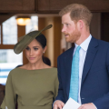 Meghan in khaki green a Stephen jones hat