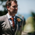 groom wearing tweed and a paper flower